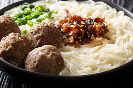 Traditional Indonesian beef meatball with noodles, fried onions, greens and broth close-up on a plate on the table. horizontal