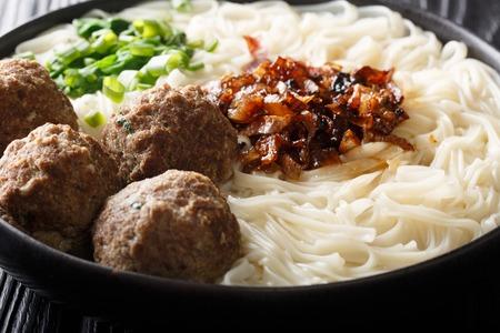 Traditionelle indonesische Rindfleisch-Fleischbällchen mit Nudeln, gebratenen Zwiebeln, Gemüse und Brühe Nahaufnahme auf einem Teller auf dem Tisch. horizontal