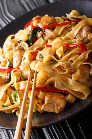 Thai traditional drunken noodles with chicken, basil, chili pepper and sauce close-up on a plate on the table. vertical