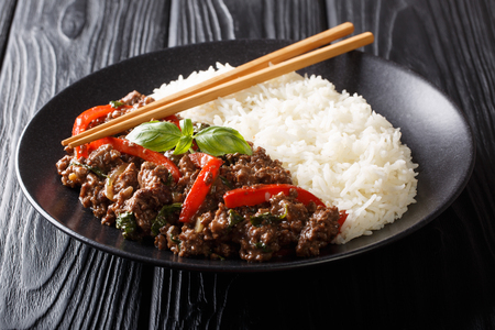 Traditional Thai Basil Beef, or Pad Gra Prow over white rice closeup on a plate on the table. horizontal