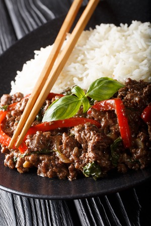 Thai Basil Beef, or Pad Gra Prow with rice side dish close-up on a plate on the table. Vertical