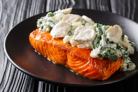 Baked Florentine salmon with creamy wine sauce, seasoned with roasted spinach and mushrooms closeup on a plate on the table. horizontal