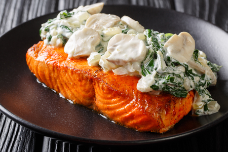 Florentine Salmon is simmered in a creamy wine sauce and topped with sauteed spinach and mushrooms close up on the plate on the table. horizontal