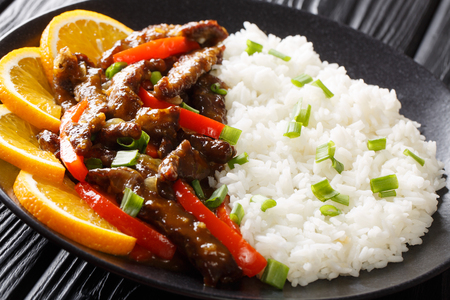 Salteado de ternera asiática con pimiento en salsa de soja y naranja servido con primer plano de arroz en un plato sobre la mesa. horizontal