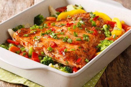 Healthy diet meal baked salmon fillet with vegetables and herbs close-up in a baking dish on the table. horizontal