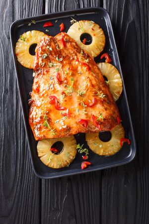 Thai cuisine of salmon fillet baked with pineapples in chili sweet sauce close-up on a plate on the table. Vertical top view from above