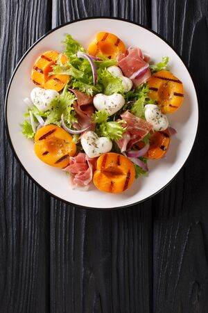 Easy dietary salad with mozzarella, prosciutto, grilled apricots, red onion and lettuce close-up on a plate on the table. Vertical top view from above Фото со стока