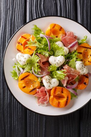 Delicious romantic salad with mozzarella, ham, apricot grilled and fresh lettuce close-up on a plate on the table. Vertical top view from above