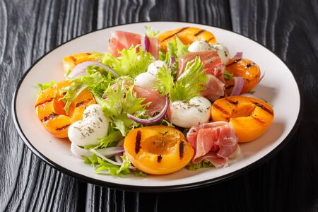 Easy recipe for summer salad with mozzarella cheese, prosciutto, grilled apricots, red onions and leaf lettuce close-up on a plate on the table. horizontal
