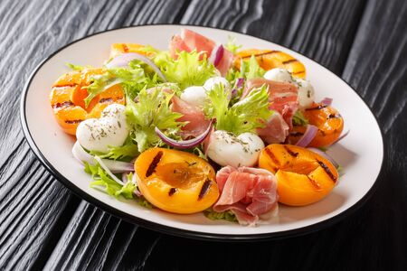 Italian summer salad with mozzarella cheese, prosciutto, grilled apricots, red onion and leaf lettuce close-up on a plate on the table. horizontal