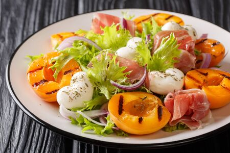 Delicious appetizer salad with mozzarella cheese, prosciutto, grilled apricots, red onion and fresh leafy lettuce close-up on a plate on the table. horizontal Фото со стока