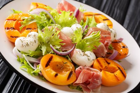 Easy dietary salad with mozzarella, prosciutto, grilled apricots, red onion and lettuce close-up on a plate on the table. horizontal