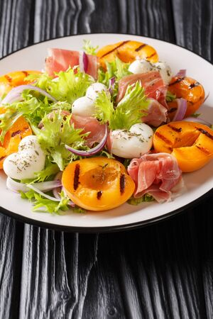 Delicate salad with mozzarella, prosciutto, grilled apricot grill and fresh lettuce close-up on a plate on the table. vertical Фото со стока