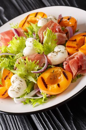 Delicious romantic salad with mozzarella, ham, apricot grilled and fresh lettuce close-up on a plate on the table. vertical