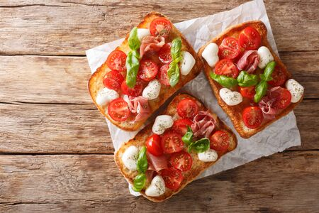 Delicious ciabatta with mozzarella, tomatoes, prosciutto and basil close-up on the table. Horizontal top view from above