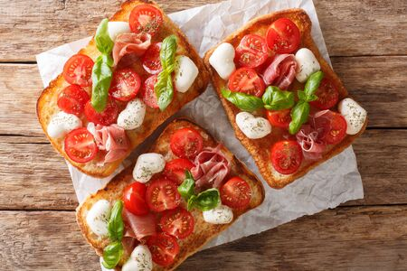 Italian open sandwiches with mozzarella, tomatoes, ham and basil closeup on the table. Horizontal top view from above