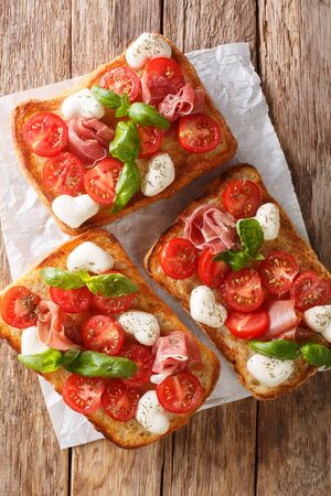 Italian open sandwiches with mozzarella, tomatoes, ham and basil closeup on the table. Vertical top view from above