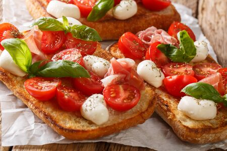 Delicious ciabatta with mozzarella, tomatoes, prosciutto and basil close-up on the table. horizontal