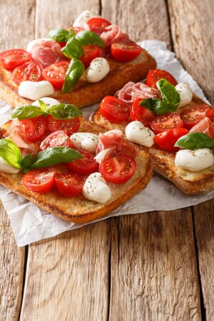 Italian sandwiches with mozzarella, tomatoes, prosciutto and basil close-up on the table. vertical Фото со стока