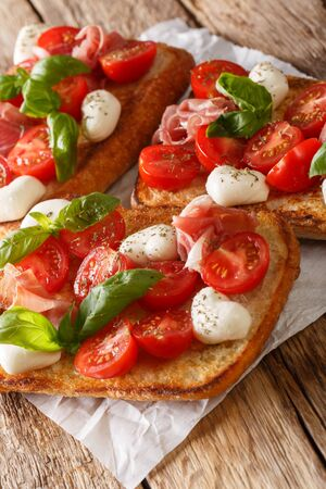 Homemade toasts with mozzarella, tomatoes, prosciutto and basil close-up on the table. vertical