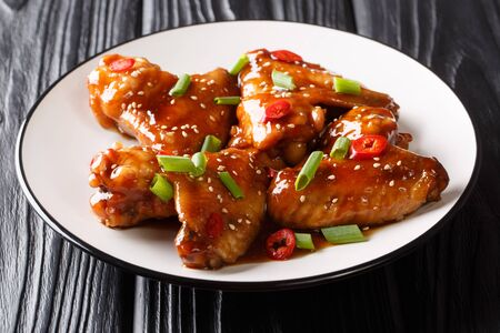 Recipe for delicious baked chicken wings with teriyaki sauce close-up on a plate on the table. horizontal