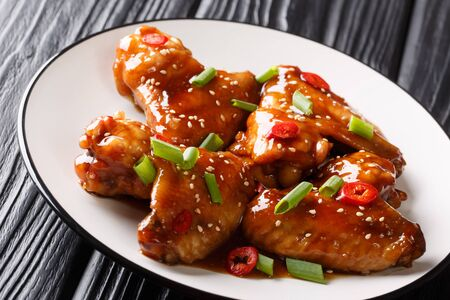 Chinese baked chicken wings with teriyaki sauce close-up on a plate on the table. horizontal