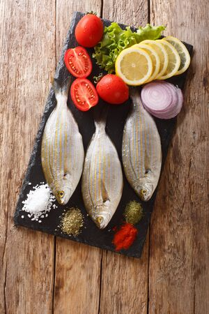 Preparation for cooking Sarpa salpa fish with lemon, vegetables and spices close-up on a slate board on the table. Vertical top view from above