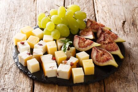 Gourmet antipasti appetizer of various cheese, fresh grapes and figs close-up on a slate board on the table. horizontal