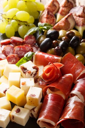 Antipasti appetizer of cheese platter, prosciutto ham, grapes, figs, sausages and olives close-up. Vertical background