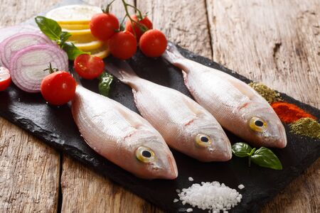 Fresh raw dorado or gilt-head sea bream fish with spices, tomatoes, onions and lemon closeup on a slate board on the table. horizontal Standard-Bild
