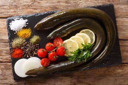 Anguille crue aux épices, légumes et citron gros plan sur une ardoise sur la table. vue de dessus horizontale d'en haut
