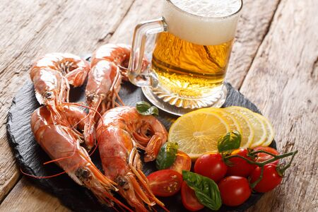 Traditional light beer and tasty shrimps, lemon and tomatoes close-up on a slate board on the table. horizontal Banque d'images