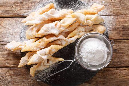 Galletas de alas de ángel recién hechas con primer plano de azúcar en polvo sobre la mesa. vista superior horizontal desde arriba