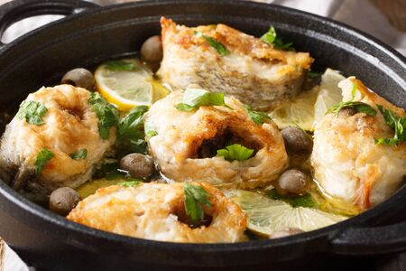 Spicy cod steaks baked with lemon and olives closeup in a pan on the table. horizontal