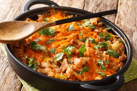 German cabbage casserole with ground beef, tomatoes, onions and cheddar cheese close-up in a pan on the table. horizontal