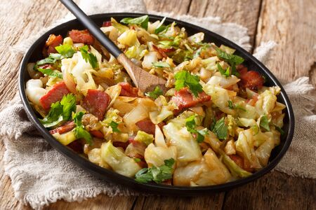 Appetizer of fried white cabbage with bacon closeup on a plate on a wooden table. horizontal