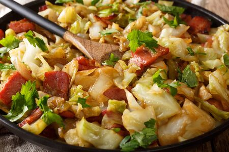 Stir fried cabbage with crispy bacon closeup on a plate on a wooden table. horizontal