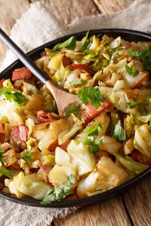 Close-up of South American fried cabbage with crispy bacon on a plate on the table. vertical