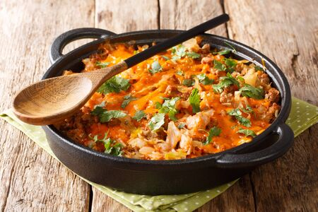 Baked homemade cabbage with ground beef, tomatoes, onions and cheddar cheese close-up in a pan on the table. horizontal