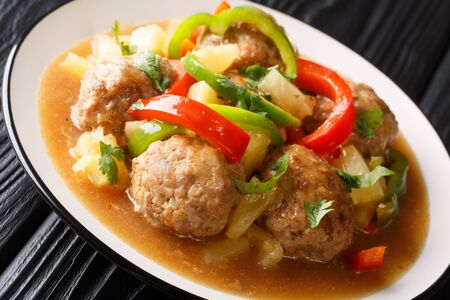 Meatballs cooked with fresh pineapples and vegetables in a sweet and sour sauce closeup on a plate on the table. horizontal
