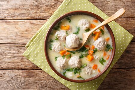 Bulgarian chorba topcheta soup with meatballs, yogurt and vegetables close-up in a bowl on the table. Horizontal top view from above