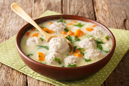 Fresh thick soup with meatballs, yogurt, rice and vegetables close-up in a bowl on the table.
