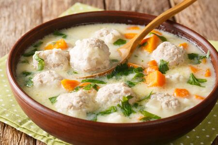 Bulgarian chorba topcheta soup with meatballs, yogurt and vegetables close-up in a bowl on the table. Stock Photo