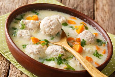 Homemade Bulgarian soup with meatballs and vegetables close-up in a bowl on the table.