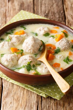 Tasty Bulgarian soup topcheta with meatballs close-up in a bowl on the table.