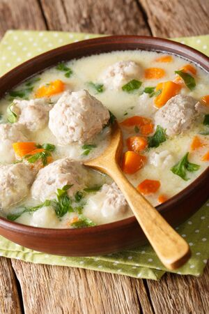 Traditional bulgarian soup with meatballs close-up in a bowl on the table. vertical