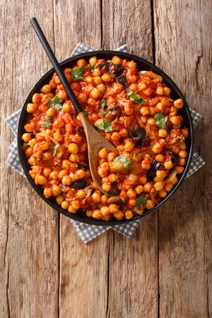Tasty fried chickpeas with eggplant in tomato sauce close-up on a plate on the table. Foto de archivo - 129246666