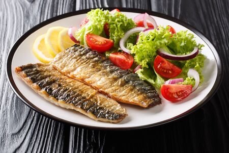 Healthy food grilled mackerel fillet with lemon and fresh vegetable salad close-up on a plate on the table. horizontal