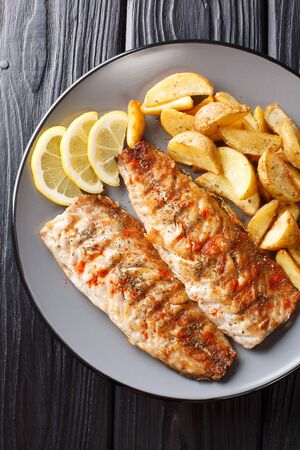 Spicy tasty grilled mackerel filet with potato wedges and lemon close-up on a plate on the table. Vertical top view from above