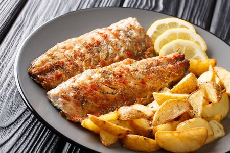 Grilled mackerel filet served with fried potatoes and lemon slices closeup on a plate on the table. horizontal Stok Fotoğraf - 129699855